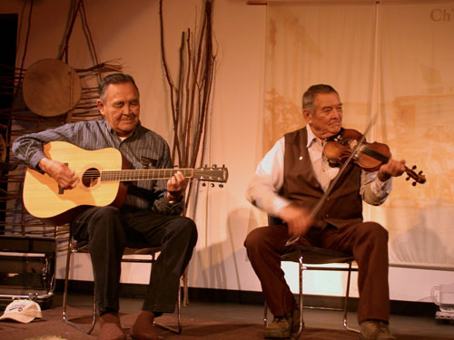 Tr'ondëk Hwëch'in Elder Edward Roberts and Tahltan fiddler Gerald Edzerza from Watson Lake share old time music traditions at a fiddle music showcase, 2005.