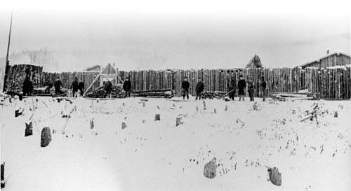 Mounties on firewood detail outside the palisade walls of Fort Constantine, winter of 1895-96.