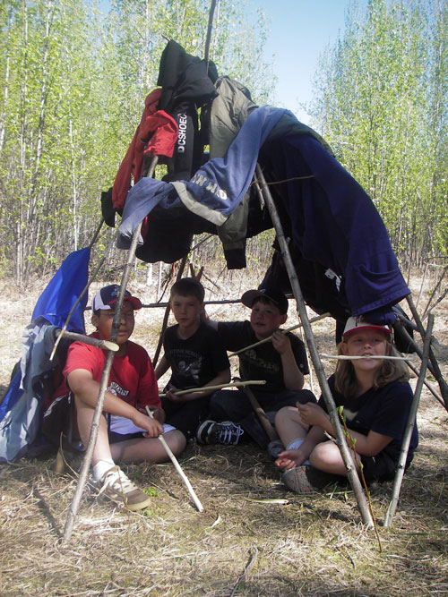 Robert Service School students try out their home-made shelter.