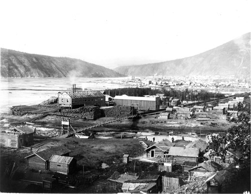 View of  Klondike Island, 1900. Notice the toll bridge crossing Klondike Island, the Klondike Mill building under construction and houses perched on the lower slopes of Klondike Hill.
