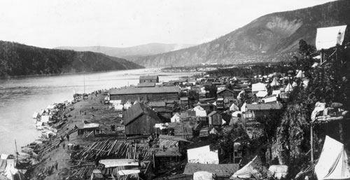 Klondike City looking north in 1898. Notice the tents, cabins and caches built on housing platforms on Klondike Hill. The large long building was Tom O'Brien's store.