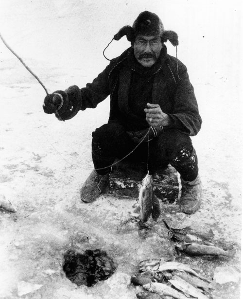 Chief Isaac ice-fishing for grayling, ca. 1900.