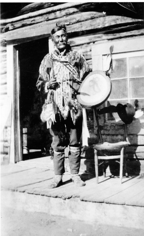 Chief Isaac poses on the porch of his cabin at Moosehide.
