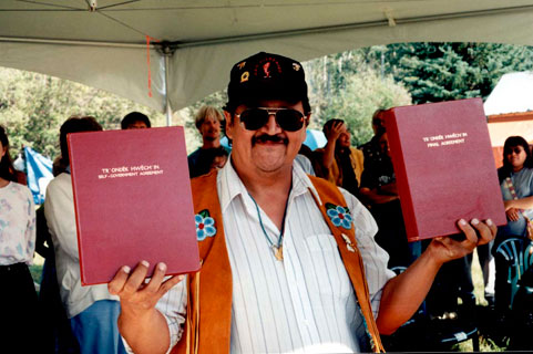 Chief Steve Taylor proudly displays the Tr'ondëk Hwëch'in final agreement at the official signing at Moosehide in 1998.