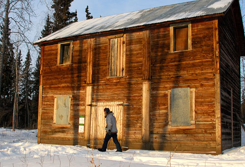 Harvey Van Patten by the NWMP detachment building, built in 1901 after the Mounties left Fort Constantine and moved across the river. The detachment moved into a smaller cabin after this building proved too large and difficult to heat. The building has been stabilized with a new foundation, strengthening of the interior structure and a new main beam.