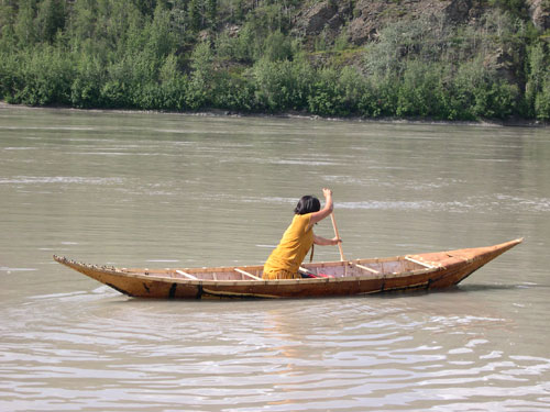 Georgette McLeod paddles a birchback canoe in the Yukon River. We created a replica of one of our ancestral watercraft.